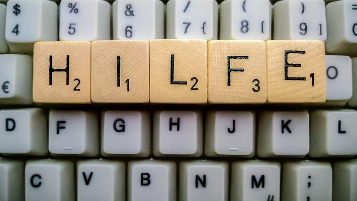 Das Wort Hilfe mit Scrabble-Buchstaben auf einer Tastatur gelegt