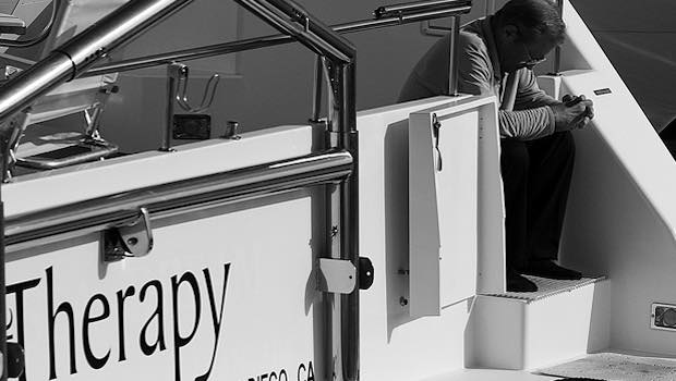 Mann auf Boot geknickt Schrift Therapy