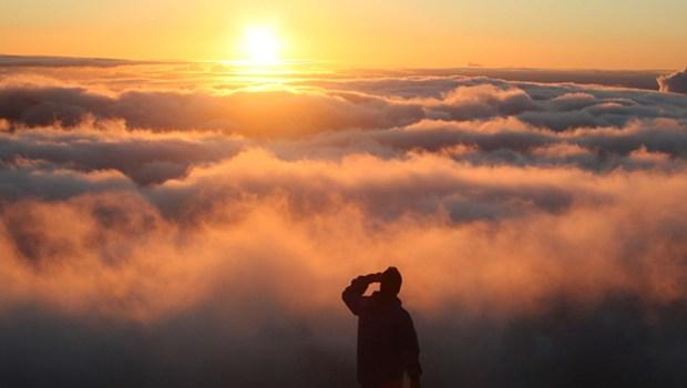 Mann vor Wolken beim Sonnenaufgang
