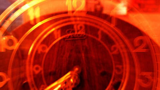 orange Uhr mit Ziffern und Zeigern