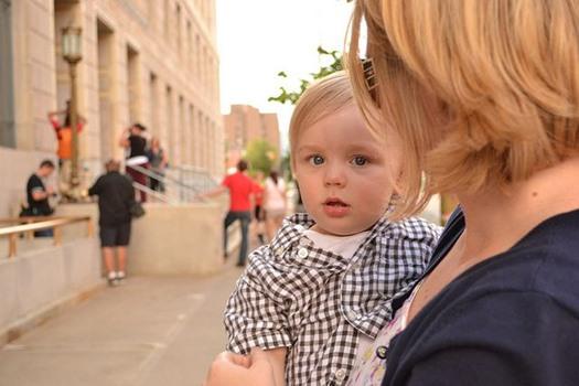 Kind auf Arm von Mutter, mit zweifelndem Blick