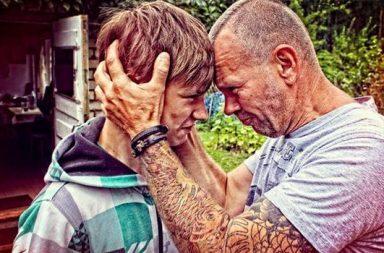 Vater hält Stirn des Sohnes an seine