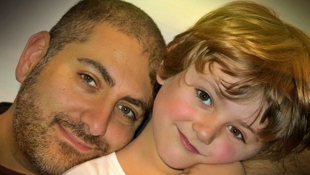 Junger Vater, kurze Haare, Bart und blonder Junge, Wange an Wange