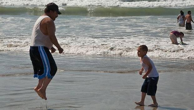 Spingender Vater mit Sohn am Strand