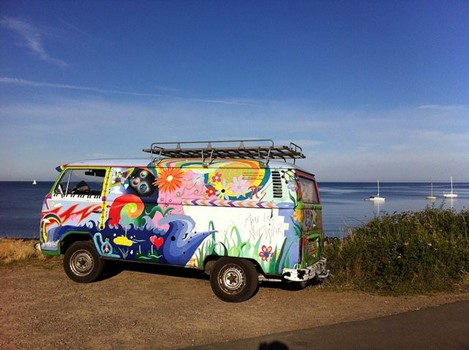 VW Bus in bunten Farben vor Meer