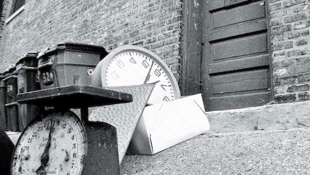 Alte Uhren, Wagen und Schrott vor einem Haus