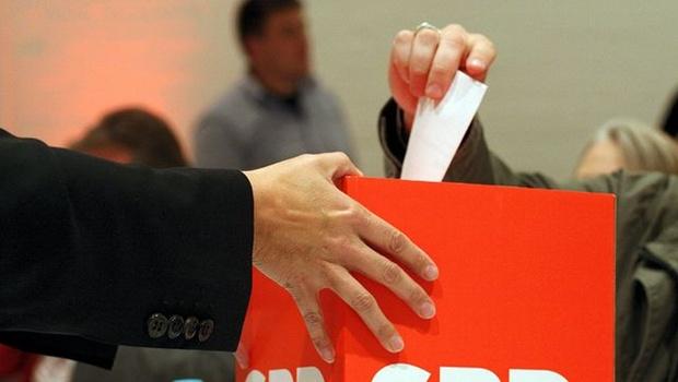 Hand mit Stimmzettel in Wahlurne