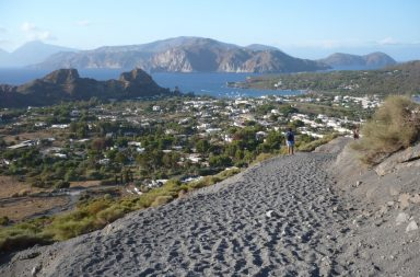 Wanderweg, Blick aufs Meer, eine Ortschaft und die Berge