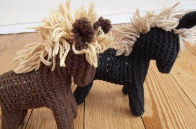 Wollspielzeugpferde, braun, schwarz, auf Holzboden