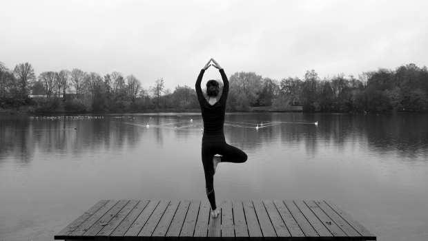 Frau auf Steg in Yogaposition