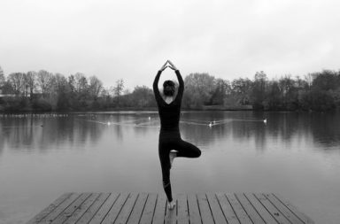 Frau macht Yoga vor einem See