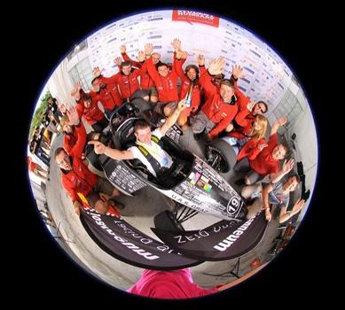 Rennwagen mit Team in Zerrspiegel