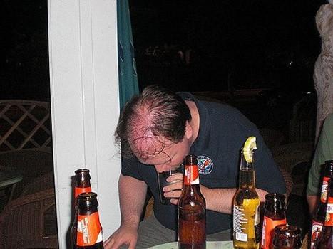 Mann  mit gesenktem Kopf, neben Flaschen