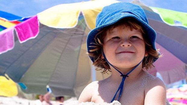 Kind am Strand mit Mütze