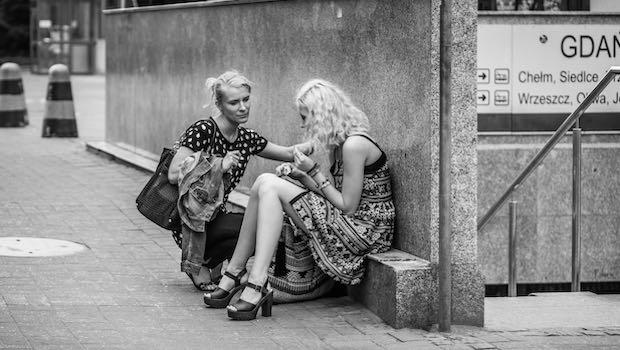zwei Frauen vor U-Bahn-Eingang, eine tröstet die andere