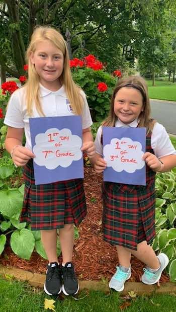 Zwei Mädchen im Schuldress mit Schildern